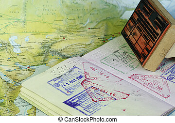 visa stamps on a passport indicting travel with map background