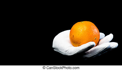 Vitamin C. The girl in white gloves holding a ripe orange on black background. Healthy food with space for text.