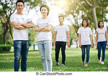 Happy young Asian volunteers standing with arms folded after cleaning garbage in city park