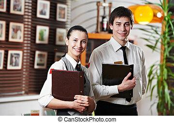 Waitress girl and waiter man in restaurant