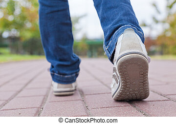 Teenager walking in sport shoes on pavement in autumn day