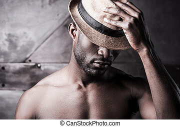 Wearing his favorite hat. Portrait of young shirtless African man adjusting his hat while standing against metal background