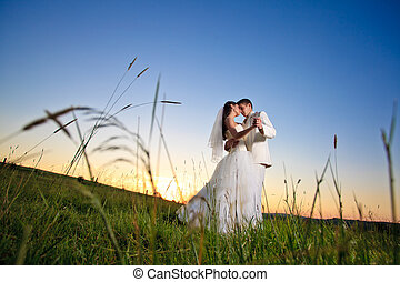 Wedding couple dansing in mountain hill on sunset
