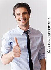 Well done! Happy young man in shirt and tie showing his thumb up and smiling while standing against grey background