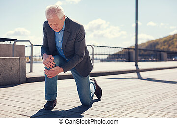 Well-dressed senior man feeling his knee after falling