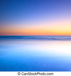 White beach, blue ocean and clear sky. Twilight sunset on background