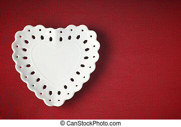 White saucer in the shape of a heart on a red background with copy space for text.