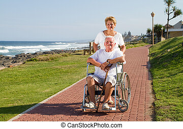 wife pushing husband in wheelchair