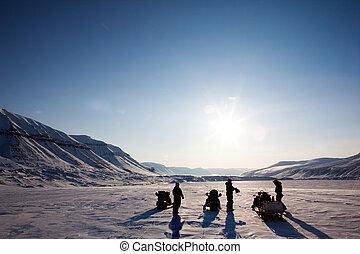 Three people on a winter snowmobile adventure in Svalbard, Norway