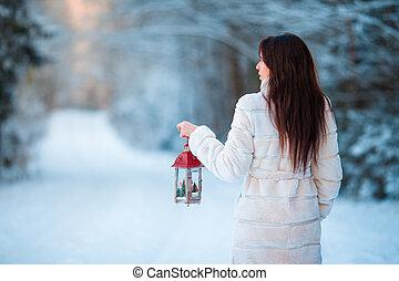 Girl holding Christmas lantern outdoors on beautiful winter snow day