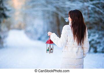 Winter beauty. Woman holding Christmas lantern outdoors on beautiful winter snow day