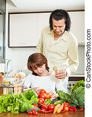 woman and handsome husband cooking together