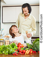 woman and handsome husband cooking with vegetables