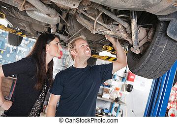 Woman and mechanic looking at car repairs