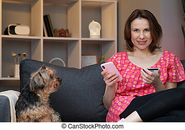 Woman are buying online with a credit card while sitting on the sofa in the living room. Women are using smartphone and doing online transactions.