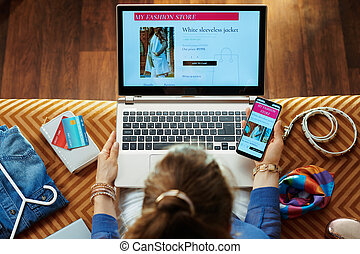 woman buying clothes while shop online on laptop and smartphone