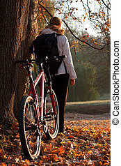 Woman cyclist with bike and backpack in autumn nature
