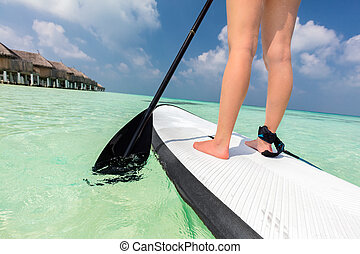 Woman does stand up paddle boarding on the ocean in Maldives