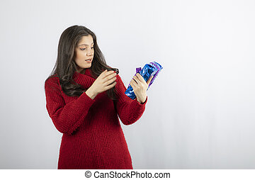 Woman excited about a Christmas gift box with purple ribbon