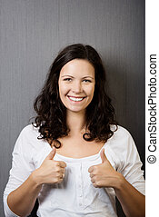 Woman Gesturing Thumbs Up Against Wall