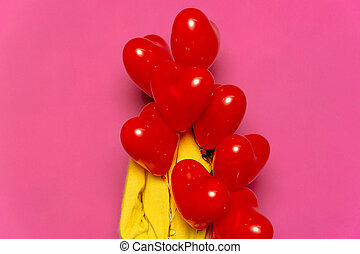 Woman hiding behind red air balloons in form of heart. Valentine's day