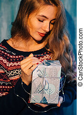 Woman holding a Christmas present.