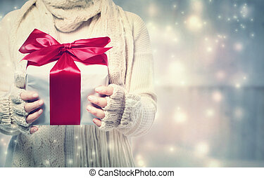Woman holding a giftbox with red ribbon