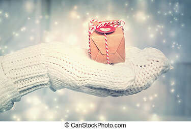 Woman holding a small gift box with heart tag