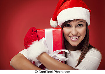 Woman holding christmas present next to her face