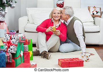 Woman Holding Christmas Present While Man About To Kiss Her
