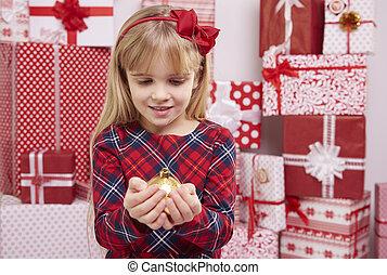 Woman holding golden Christmas ball