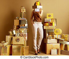 woman holding parcels and yellow piggy bank in front of face