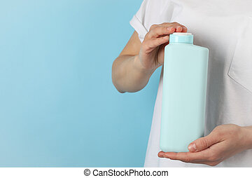 Woman holds blank shampoo bottle on blue background, space for text