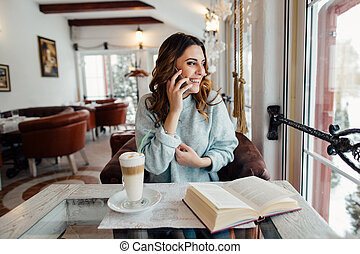 Woman in cafe talking on cell phone