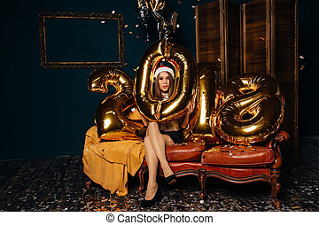 Woman in Christmas hat with golden balloons