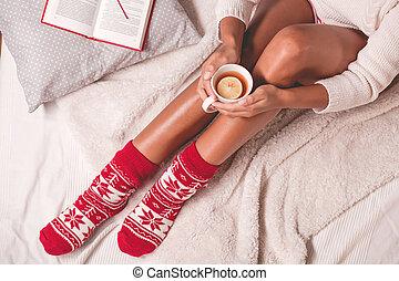 Woman in christmas socks holding mug