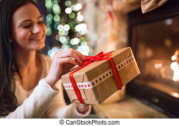 Woman in front of Christmas tree holding present.