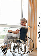 Woman in her wheelchair looking at