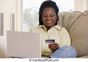 Woman in living room using laptop holding credit card and smilin