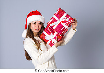 Woman in red christmas hat holding presents