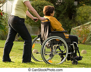 Disabled senior woman in a wheelchair with her nurse