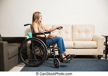 Woman in wheelchair watching TV