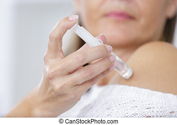 woman is doing a self injection