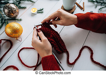 Woman knits Christmas things on white wooden background.
