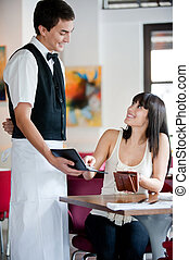 A young and attractive woman paying the bill in restaurant