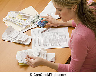 A young woman looks upset while sorting through her old receipts. Horizontal shot.