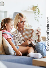 Woman reading a book to girl