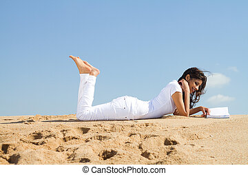 woman relaxing on beach with book