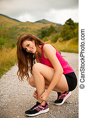 woman runner tie shoes on a mountain road