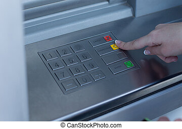 Woman selecting a transaction on a bank ATM